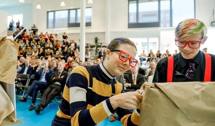 Scholieren verrichten, met de onthulling van een aantal fotokunstwerken, de officiële opening van de vernieuwde school.