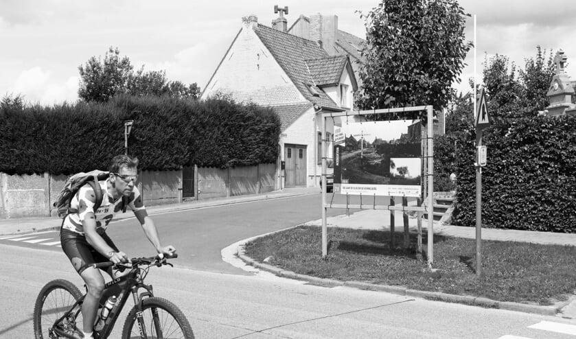 Wulvergem in de Belgische Westhoek. De man op de fiets draagt een shirt met klaprozen. De klaproos staat in Groot-Brittannië symbool voor de Eerste Wereldoorlog. Op het billboard wordt aandacht besteed aan 100 jaar Slag om de Kemmelberg