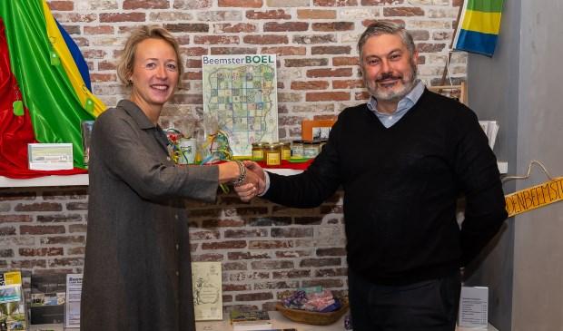 Daniëlle Woudstra en Moncef Beekhof bezegelen de samenwerking. Op de achtergrond de producten uit Beemster die nu een prominente plek hebben in de VVV-winkel.