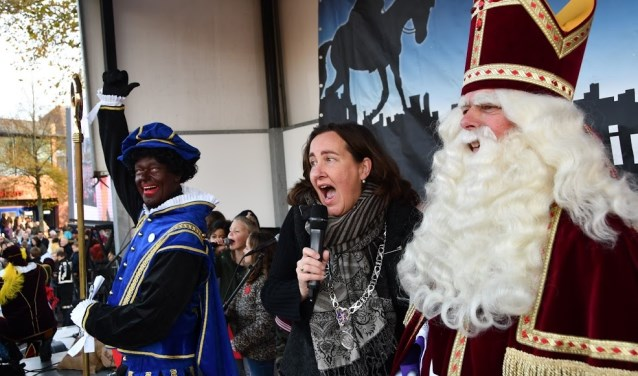 Burgemeester Baltus zingt enthousiast mee met het Heemskerks Sinterklaaslied. Piet zorgt voor een dansje terwijl de Sint aandachtig luistert.
