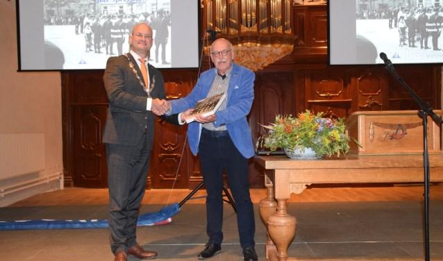 De auteur, Egbert Ottens, overhandigt het eerste boek aan burgemeester Jan Nieuwenburg.
