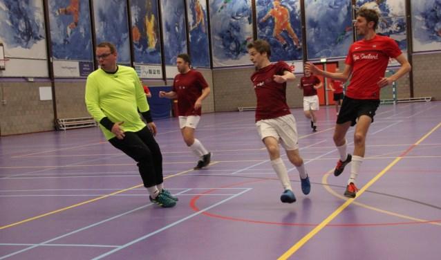 Een speler van Tips Thailand (in helder rood shirt) verschalkt de doelman van Damclub SNA.