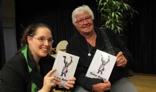 Ans Noordermeer-Peters neemt uit handen van haar kleinkind én schrijfster Geertje Owel het boek 'Oma Ansie' in ontvangst.