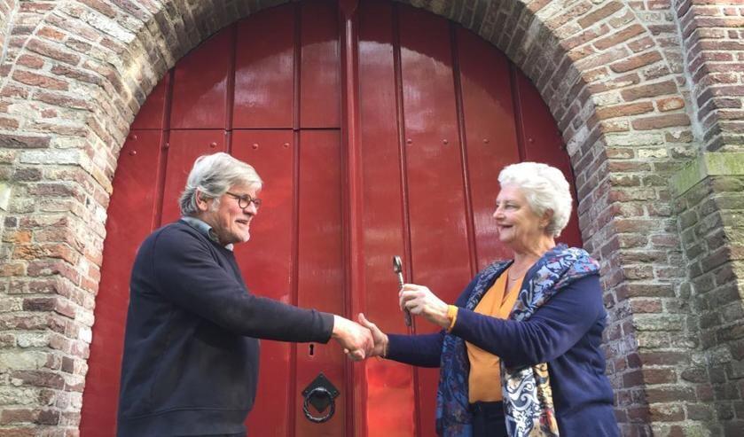 Gerda van der Kolk van de PGMWF draagt de sleutel van de kerk over aan André van Rixel van de Stichting Vrienden van de Hensbroeker Kerk.