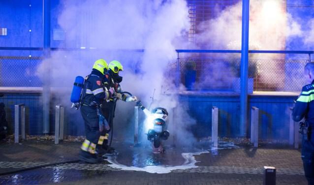 Brandweermannen blussen de brandende scooter.