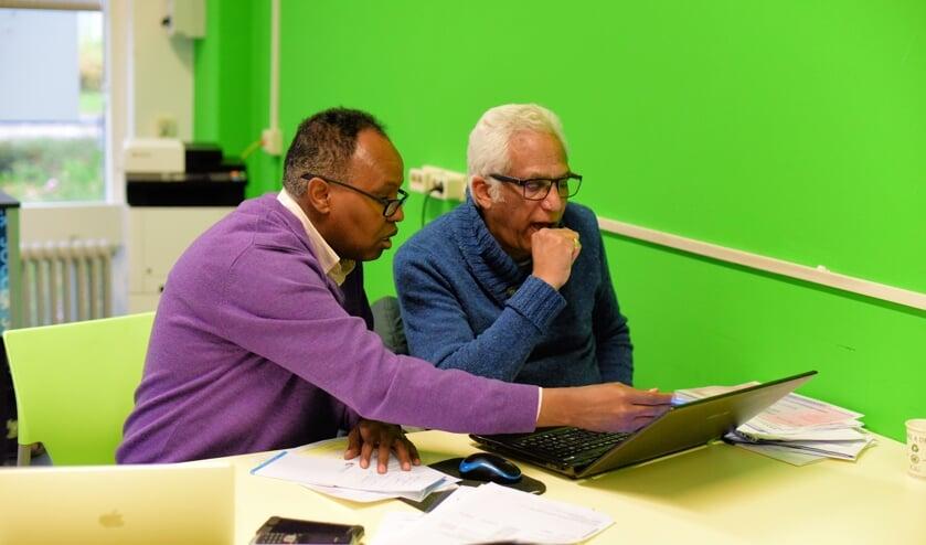 Ali Ware helpt Osama Khedr tijdens het migrantenspreekuur.