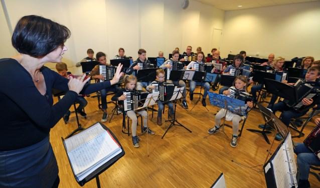Muziekdocente Bianca IJdema (l) geeft haar accordeonorkest instructies.