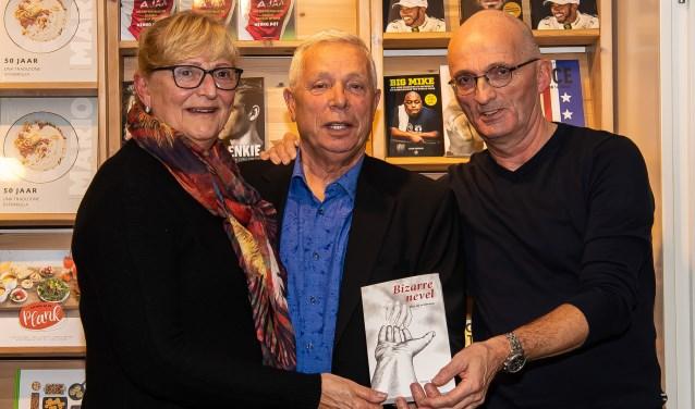 Jeroen Riemeijer (rechts) gaf het eerste exemplaar aan Paul Macco. Links Jeannette, de partner van Macco.