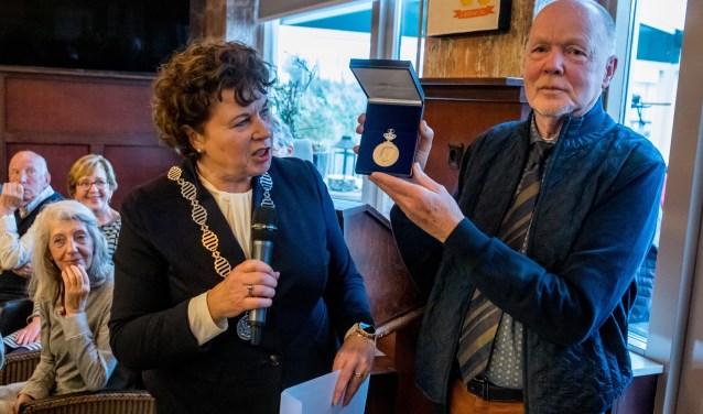 Burgemeester Kompier reikte de erepenning uit aan een zeer verraste voorzitter.
