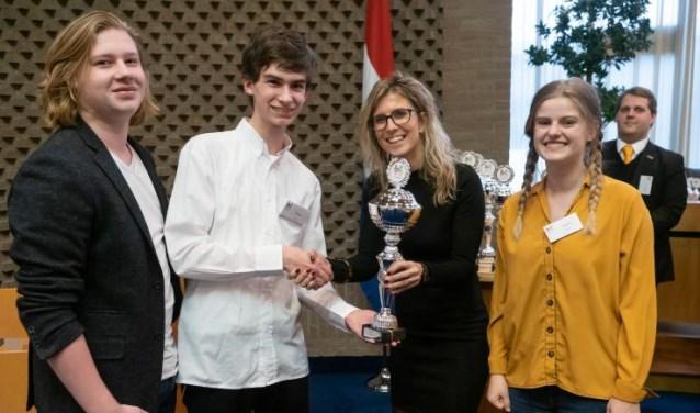 De drie finalisten van het Kaj Munk College ontvangen de beker van hockeykampioen Lisanne de Roever.