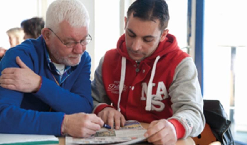 Taalmaatjes helpen een (buurt)bewoner met het oefenen van de Nederlandse taal.