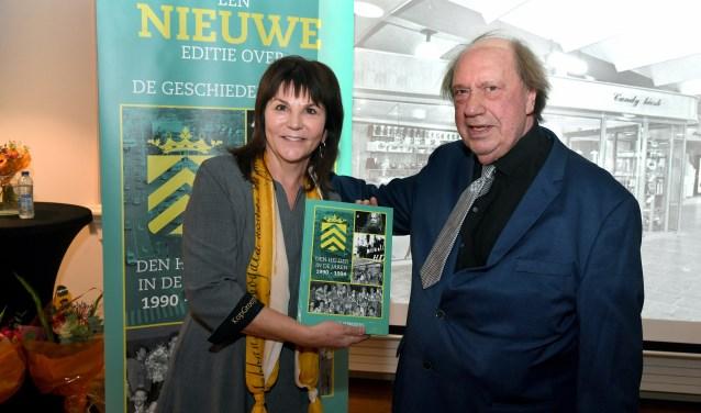 Anita Ruder van School 7 neemt het boek in ontvangst van Marinus Vermooten.