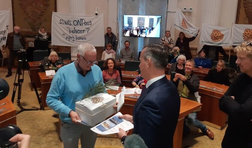 Voorzitter Jan Engelbregt biedt het burgerinitiatief aan met 8.570 handtekeningen, verlucht met een dennentak.