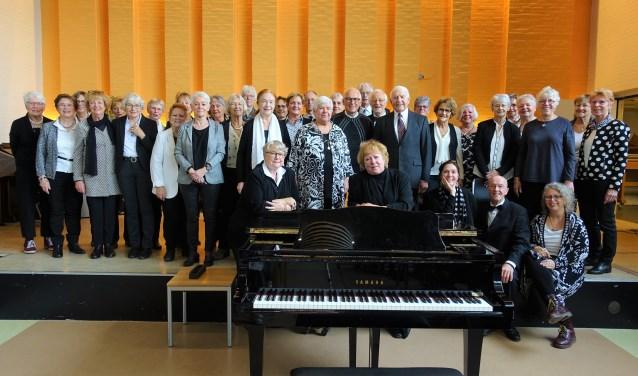Achter de piano dirigent Carole Kroese (rechts) en stemcoach Elise Blesgraaf met het voltallige koor.