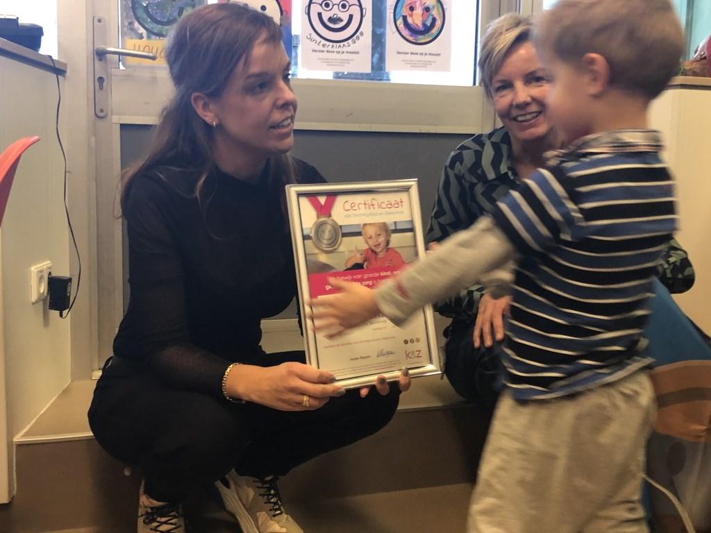 Wat verlegen loopt Christiaan (3 jaar) naar voren om de oorkonde van de Zilveren Smiley aan te nemen. (Foto: Aangeleverd) © rodi
