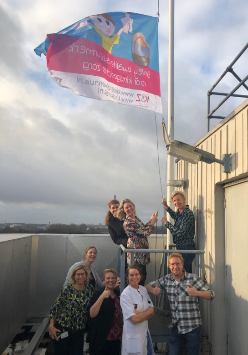 Het hijsen van de speciale Zilveren Smiley vlag op het dak van het ziekenhuis.