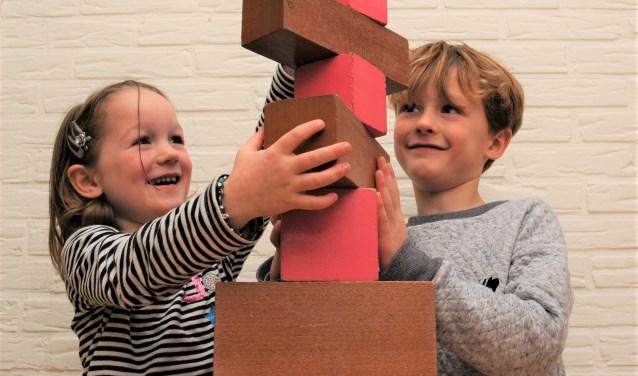 Janne en Bruno werken samen aan de roze toren en bruine trap.