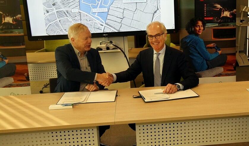 Wethouder Quakernaat en KPN-directeur Offerhaus bekrachtigen de samenwerking met een handdruk.