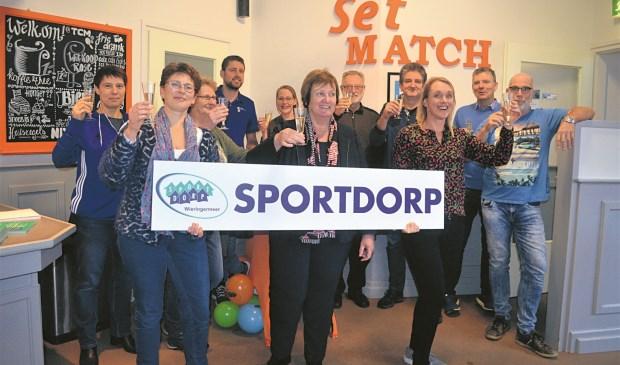 Wethouder Mary van Gent toont een Sportdorp-bord temidden van de partners van Sportdorp Wieringermeer.