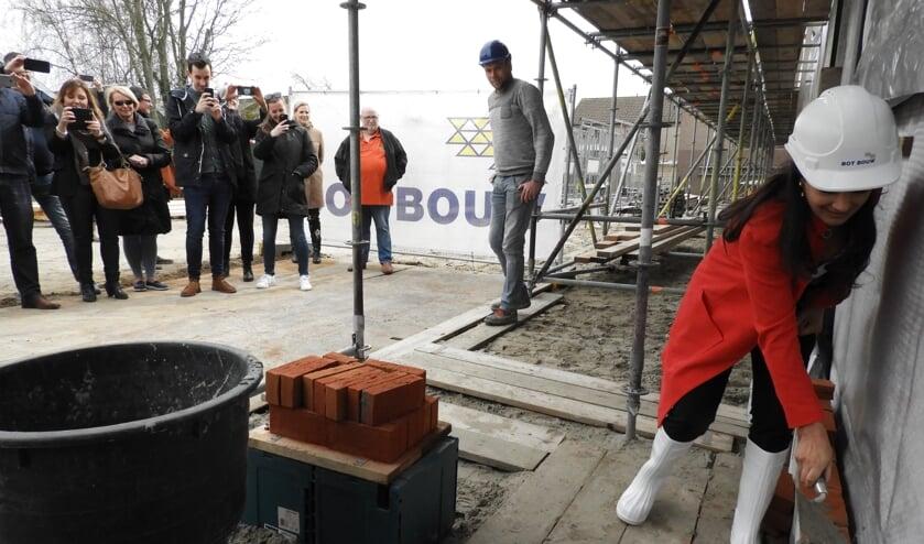 Bewoners maken foto's van de eerste steenlegging door de wethouder.