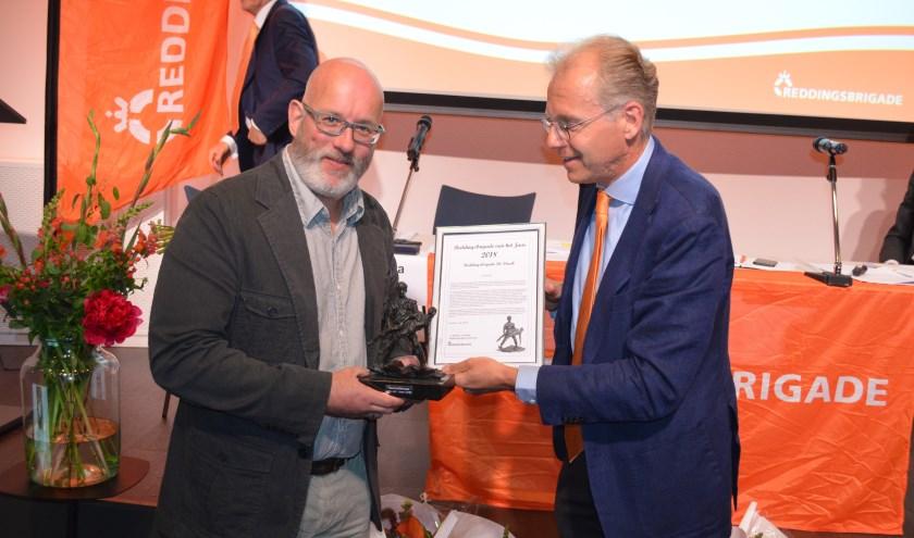 Voorzitter Bob Koelman neemt de trofee Reddingsbrigade van het Jaar in ontvangst.