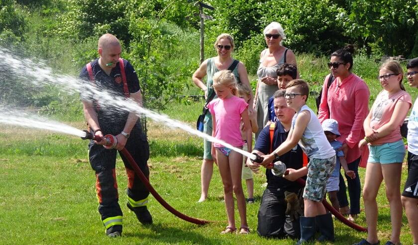 Kinderen mogen spuiten met een echte brandweerslang.