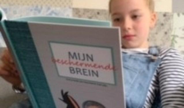 Meisje dat boek 'Mijn beschermende brein' leest.