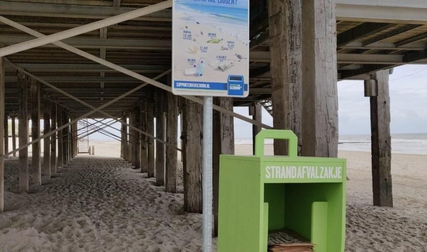 Speciale houders met papieren afvalzakjes neergezet bij de strand etablissementen