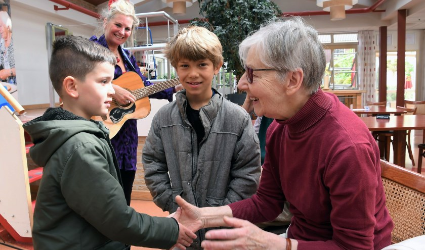 Six en Joah met een mantelzorgster, op de achtergrond zangjuf Jessica van Noord.