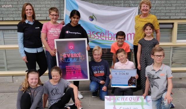 Trots hebben de kinderen van De Hasselbraam de cheque overhandigd aan Aletta Troost van Unicef (staand links).