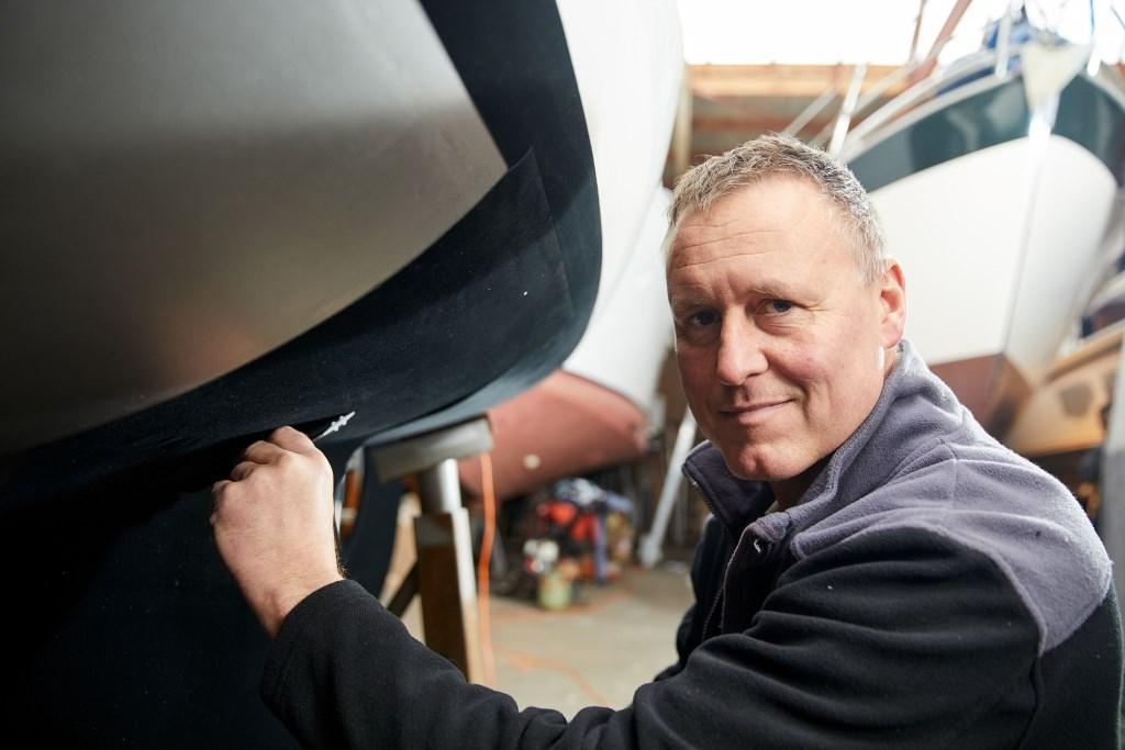Rik Breur plakt het door hem uitgevonden zelfklevend antifouling 'tapijt' op een boot.  (Foto: PR) © rodi
