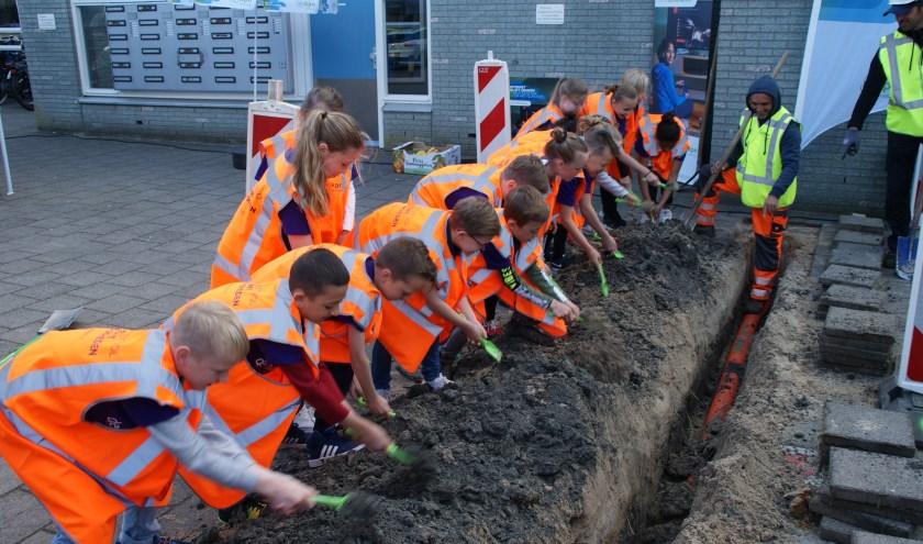 Leerlingen van De Hasselbraam mochten het zand weer terug de geul in scheppen.