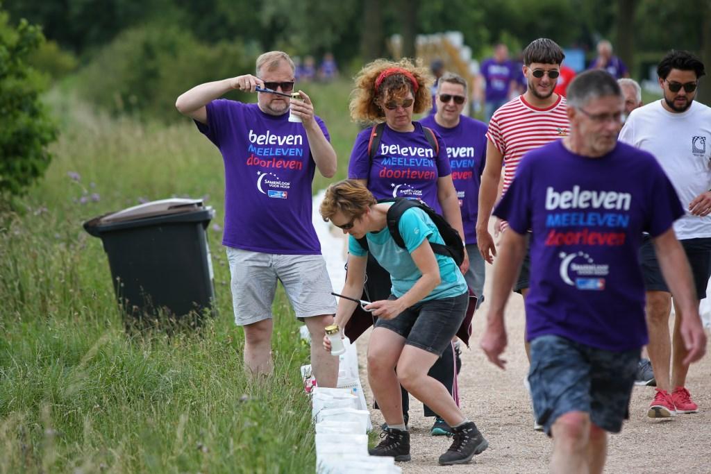 Deelnemers steken kaarsen aan die in kaarsenzakken langs de route staan.  (Foto: Rowin van Diest) © rodi