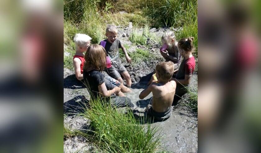 Kinderen ontdekken hoe je met modder kunt spelen. De kleren blijven niet schoon!