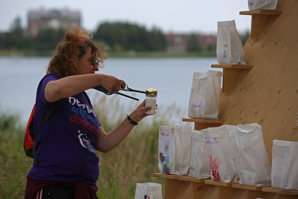 Een deelnemer steekt een kaars aan voor een dierbare.  (Foto: Rowin van Diest) © rodi