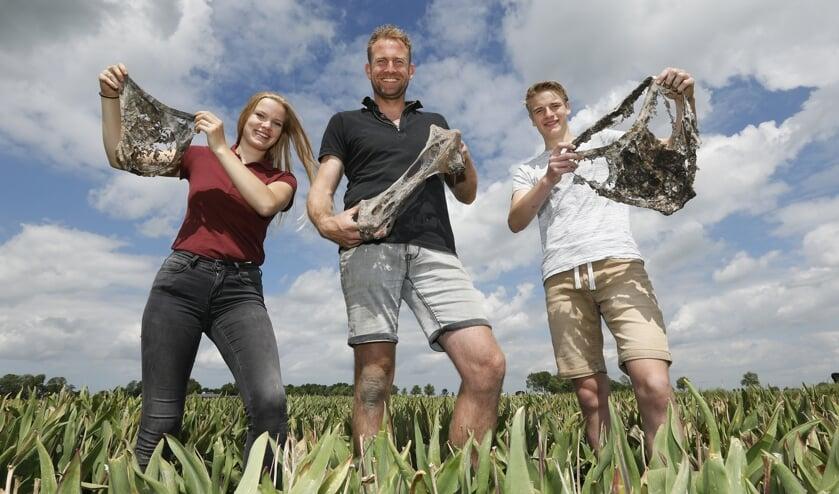 Vlnr: Karlijn van Andel (studente Clusius College), tulpenboer Tom Groot en Rowin Hartman Kok (student Clusius College) met hun opgegraven onderbroeken.