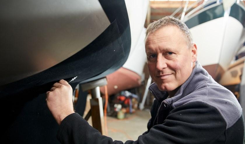 Rik Breur plakt het door hem uitgevonden zelfklevend antifouling 'tapijt' op een boot.