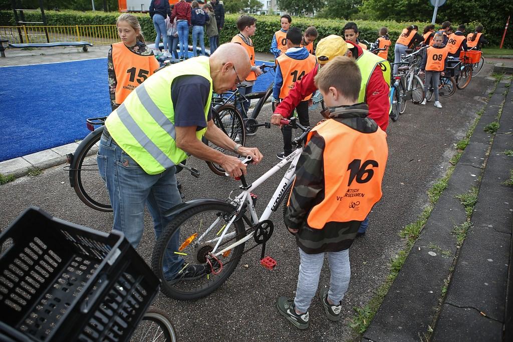 Alvorens de kinderen mogen starten aan het praktisch examen worden hun fietsen gecontroleerd.  (Foto: Rowin van Diest) © rodi