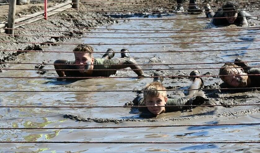 De strak gespannen touwen boven het modderbad dwingen de deelnemers diep te gaan.