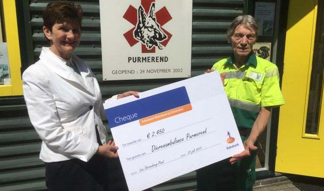Pim Langereis van de Dierenambulance krijgt de cheque van de afscheid nemende Lea Sterenborg-Pinxt.