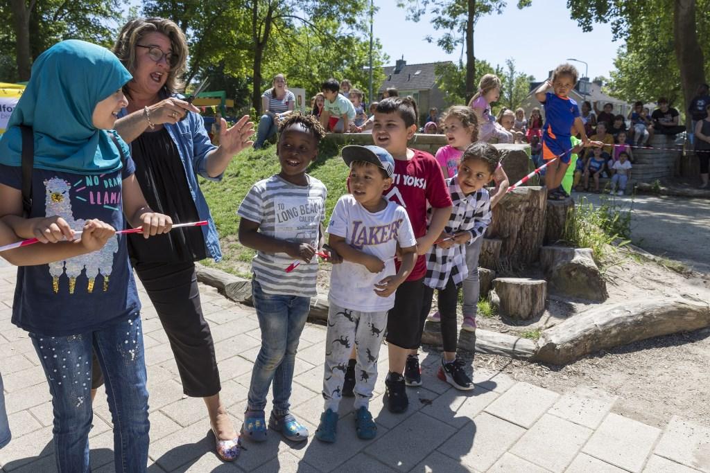 Wethouder Marjolein Steffens knipt het lint van kinderen door; het Wereldplein is geopend.  (Foto: Vincent de Vries) © rodi