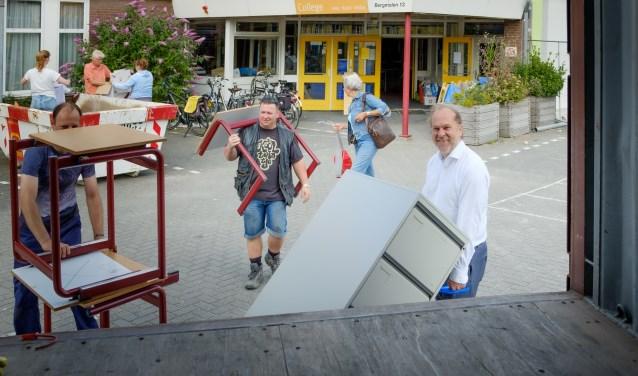 Burgemeester Bert Blase (r) helpt bij het inladen van meubelstukken voor Stichting Miss IQ.