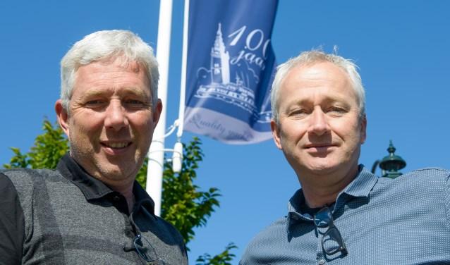 Klaas en Albert Hakvoort voor de vlag met het logo van de 100-jarige.