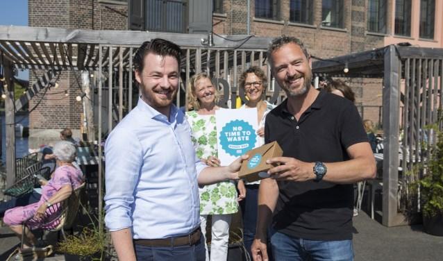 Links wethouder Robbert Berkthout die Frank van Baaren, eigenaar van restaurant Frisk aan het Spaarne en bestuurslid Koninklijke Horeca Nederland, het eerste exemplaar aanbiedt.