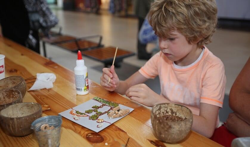 Kian is geconcentreerd bezig met zijn creatieve zomermozaïek.