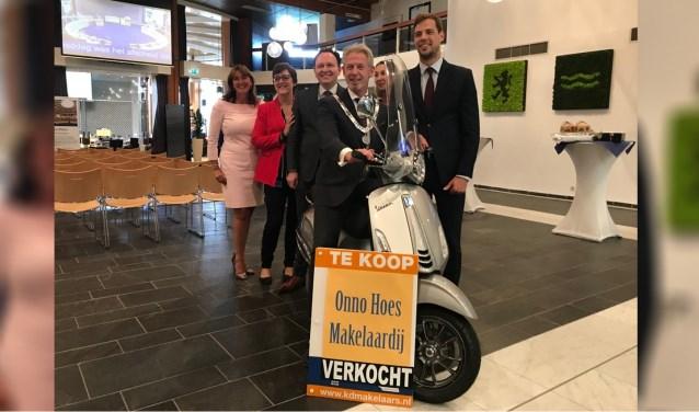 Waarnemend burgemeester Onno Hoes poseert in de raadszaal op de zojuist overhandigde makelaarsscooter.