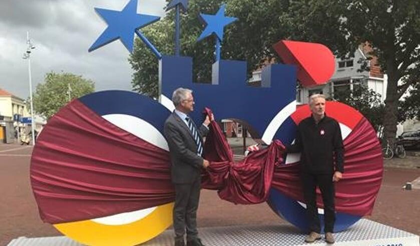Wethouder Pieter Dijkman en Vincent Thijssen onthullen deze supergrote fiets op station Alkmaar.