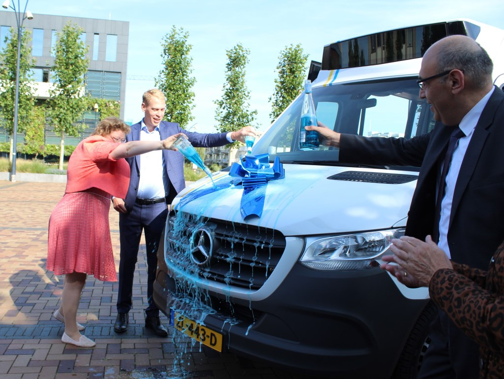 Annette Valent (wethouder Heerhugowaard), Nils Langedijk (wethouder Langedijk) en gedeputeerde Adnan Takin van de Provincie, dopen de nieuwe bus.  © rodi