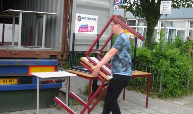 Schoolmeubilair wordt in de vrachtcontainer geladen.