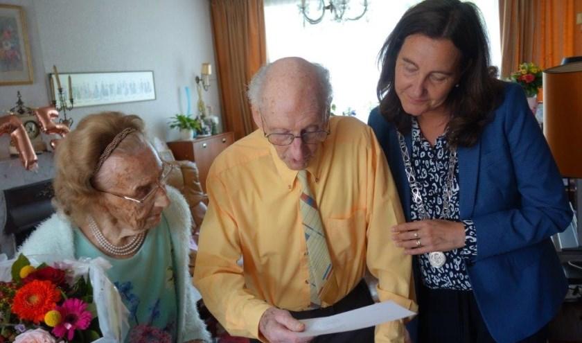 Burgemeester Baltus (rechts) heeft een brief van de Koning voor het jubileumpaar. De heer De Looze leest de brief.